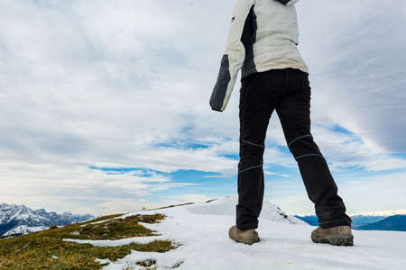Low angle view of person walking on snow covered mountain ridge.