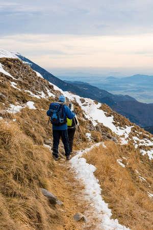 Par de excursionistas descendiendo traile de invierno de pendiente cubierta de hierba.