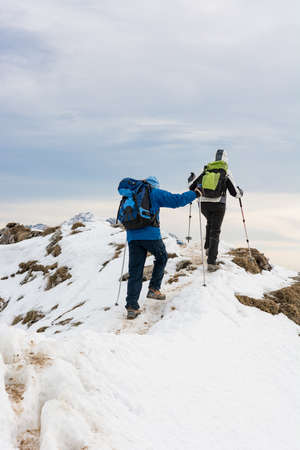 Pair of mountaineers ascending a snow covered mountain ridge.