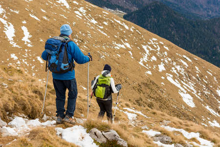 Pair of hikers descending winter traile of grass covered slope.