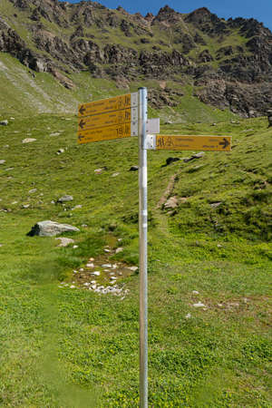 Yellow sign post indicating different hiking trails above Valnontey area. Stockfoto