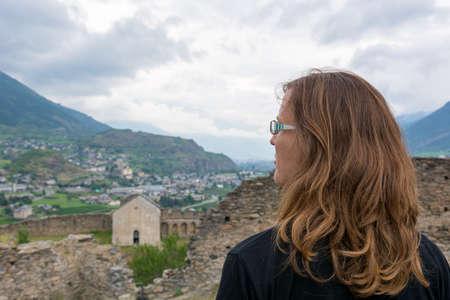 Attractive brunette looking across old italian town.