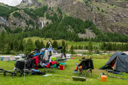 Female camper drying wet clothes after heavy storm in mountain camping.