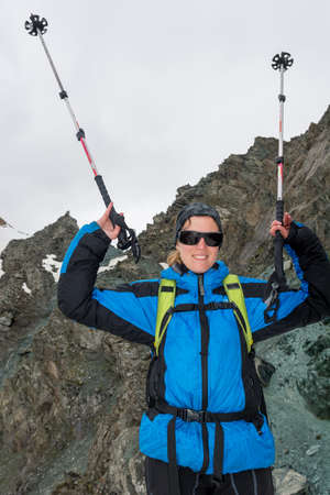 Female mountaineer celebrating ascend with walking poles raised high.