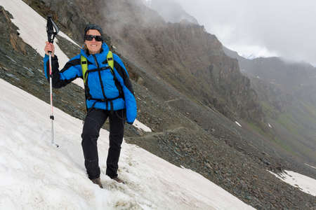 Female mountaineer standing on a snowy slope in the mountains.