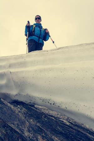 Female mountaineer standing on top of melting snow ridge.