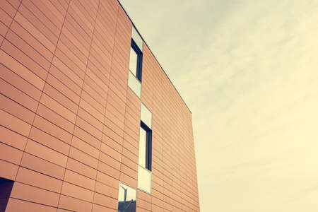 Architecture detail of modern building with orange facade and windows reflecting the sky. Stock fotó - 138172386
