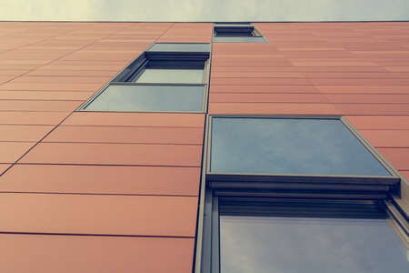 Architecture detail of modern building with orange facade and windows reflecting the sky. Stock fotó - 138175827