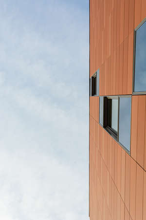 Architecture detail of modern building with orange facade and windows reflecting the sky.