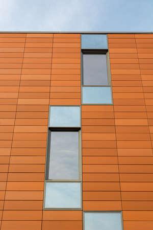 Détail de l'architecture du bâtiment moderne avec façade orange et fenêtres reflétant le ciel. Banque d'images