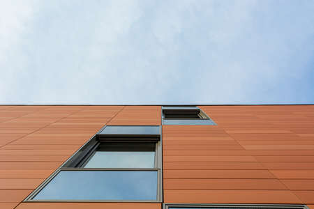 Architecture detail of modern building with orange facade and windows reflecting the sky. Upwards view. Stock fotó - 138195976