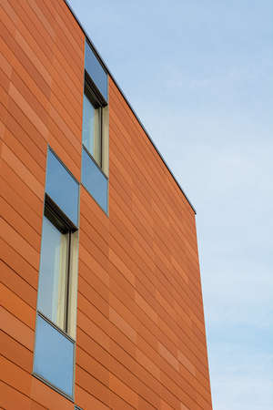 Architecture detail of modern building with orange facade and windows reflecting the sky. Upwards view.