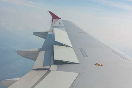 Airplane wing view from the passenger seat. Flying high above clouds.