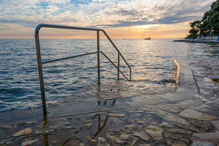 Ocean sunrise with metal fence leading swimmers into water.