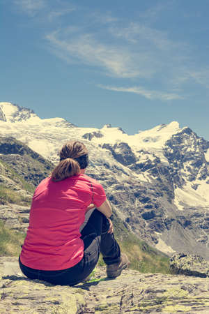 Rear view of attractive brunette meditating in picturesque mountains. Retreat from busy every day lifestyle.