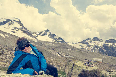 Female mountaineer resting on a rock surrounded by spectacular mountain views. Active lifestyle. Archivio Fotografico