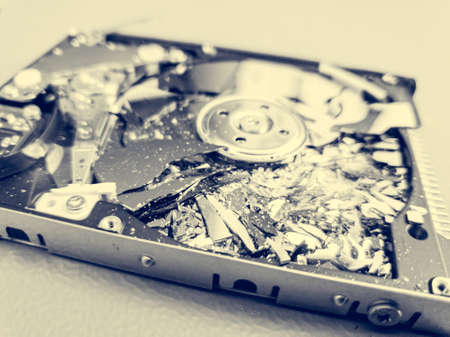 Shattered platter of computer hard drive disk. Destroying sensitive information - cyber security.