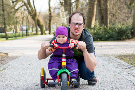 Baby girl and her dad posing on a children bike in a park.