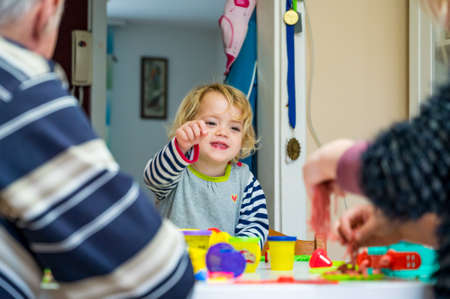 Cute girl playing with many colorful doughs surrounded with unrecognizable family members.