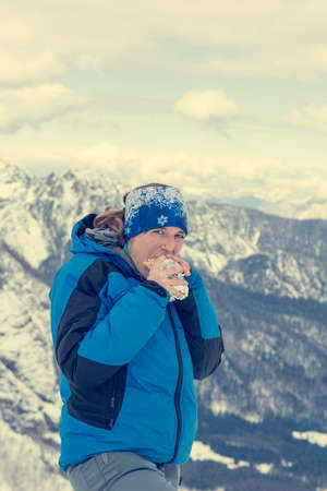 Female mountaineer eating a sandwich in snow covered mountains. Reklamní fotografie