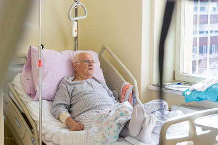 Elderly man laying on a bed in hospital. Banque d'images