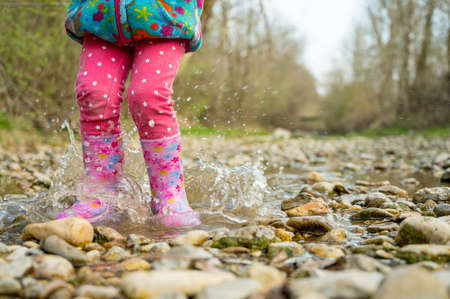 Young girl walking along a shallow stream with rubber pink boots.