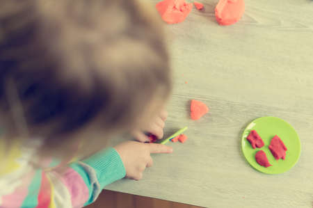 Detail of child having fun playing with colorful dough at home.
