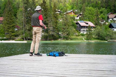 Fisherman standing on wodden pier catching fish.