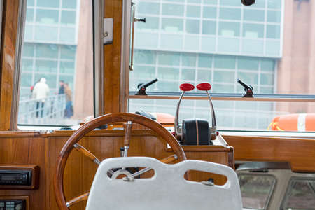Boat interior with old luxurious wooden steering wheel. Banque d'images