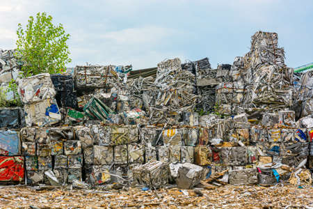 Compressed aluminium scrap in large cubes forming landfill in piles. Reusing and recycling waste material.