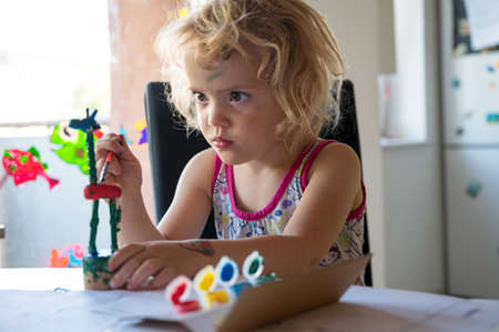 Cute girl painting wooden giraffe push puppet.