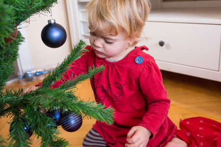 Cute blonde girl decorating Christmas tree with many ornaments. 版權商用圖片