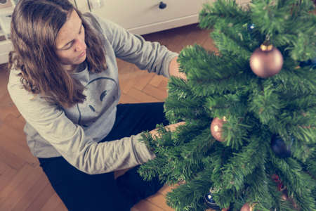 Woman wearing casual clothes decorating Christmas tree with many ornaments.