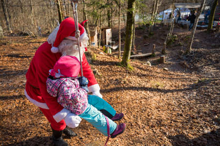 Santa claus helping a girl to swing in park.