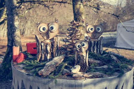 Three wooden owls on a decorated table.