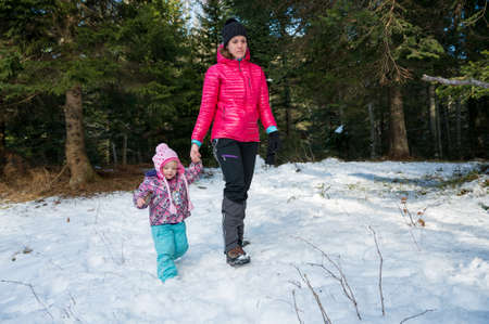 Mother and daughter walking through winter forest.