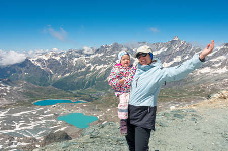 Happy mother holding her daughter surrounded with picturesque mountain landscape.