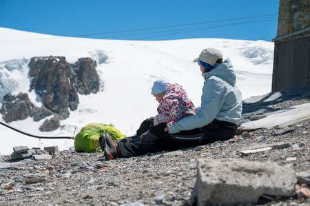 Mother and daughter sitting on floor enjoying the view of summer ski resort. Foto de archivo
