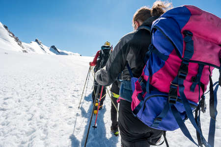 Rope team member point of view with mountaineers walking on snow and ice in sunny weather. Foto de archivo