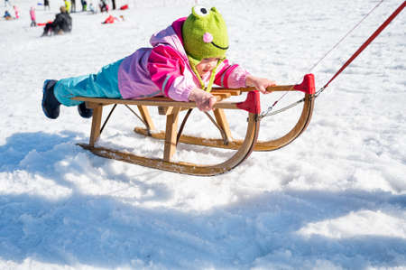 Cute girl on a sledge being pulled by her mother. Stok Fotoğraf