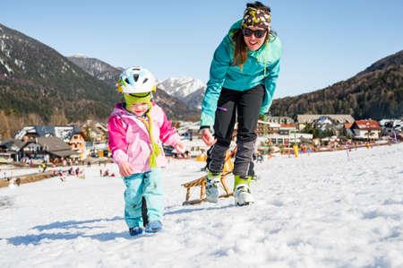Cute girl having fun with her mother on ski resort.