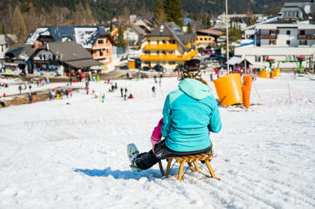 Rear view of mother and daughter rushing down slope on a sledge.