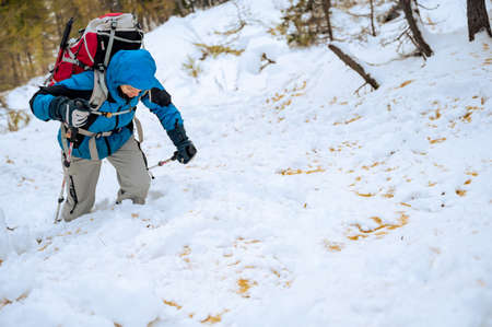 Female mountaineer in full winter gear surrounded with snowy forest. Foto de archivo