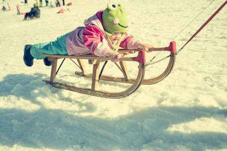 Cute girl on a sledge being pulled by her mother.