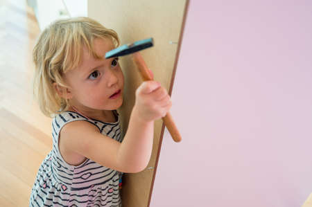 Cute blonde girl renovating her room building a closet.
