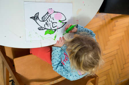 Cute girl drawing a fish using glass colors at home. Banque d'images