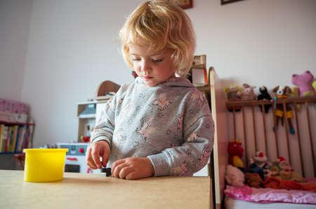 Cute blonde girl renovating her room building a closet. Stockfoto