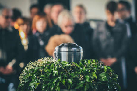 A metal urn with ashes of a dead person on a funeral, with people mourning in the background on a memorial service. Sad grieving moment at the end of a life. Last farewell to a person in an urn. Standard-Bild