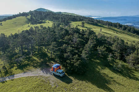 Aerial photo of a van with a tent on the back on the top of the mountain. Off grid camping in wild forests, away from civilisation, modern nomad.