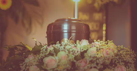 A metal urn with ashes of a dead person on a funeral with noone around on a memorial service. Sad grieving moment at the end of a life. Last farewell to a person in an urn. Imagens